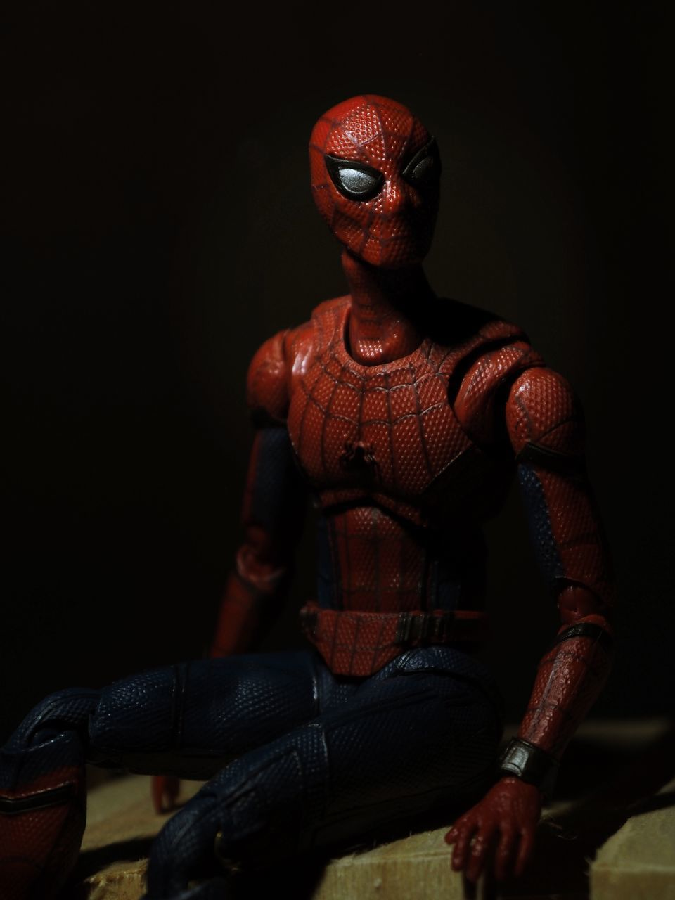 MIDSECTION OF MAN SITTING AGAINST RED TOY