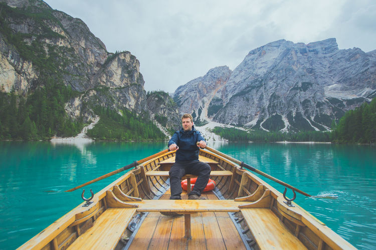 Man rowing boat in lake against mountains