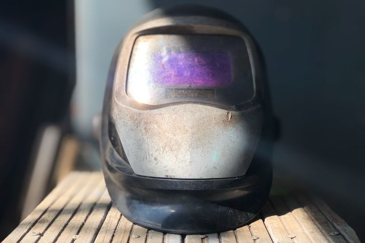 Close-up of old welding helmet on table