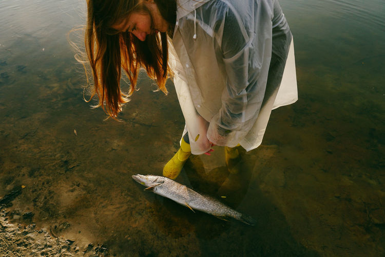 Woman standing by dead fish at lakeshore