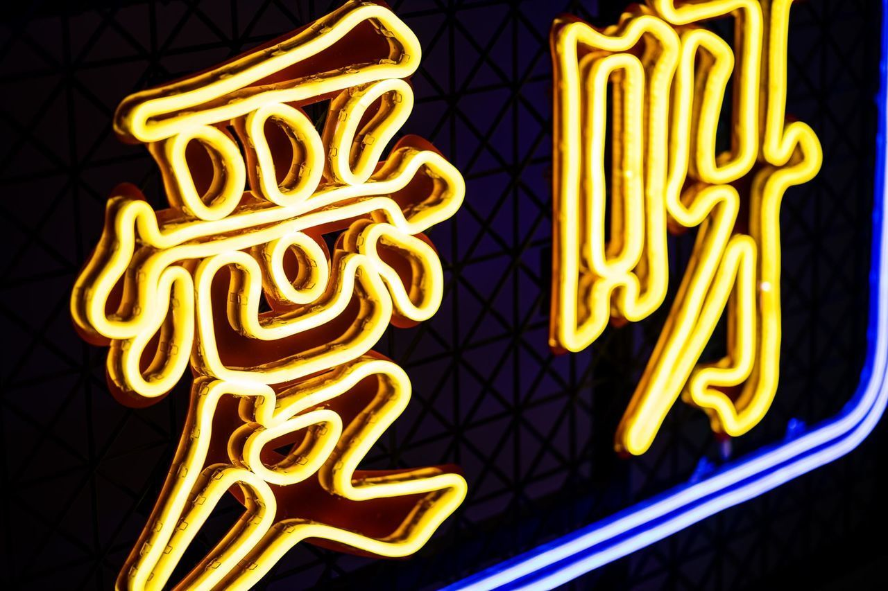 LOW ANGLE VIEW OF ILLUMINATED TEXT ON YELLOW LIGHT