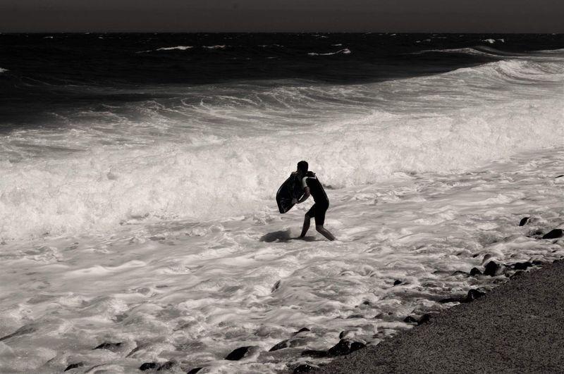 Surfer walking at beach