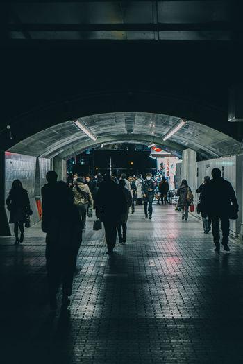 Group of people walking on railroad station platform