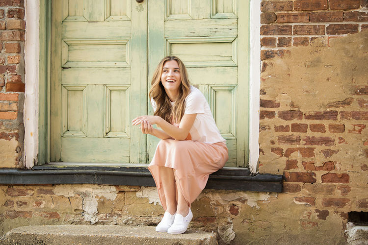 Smiling young woman sitting against door