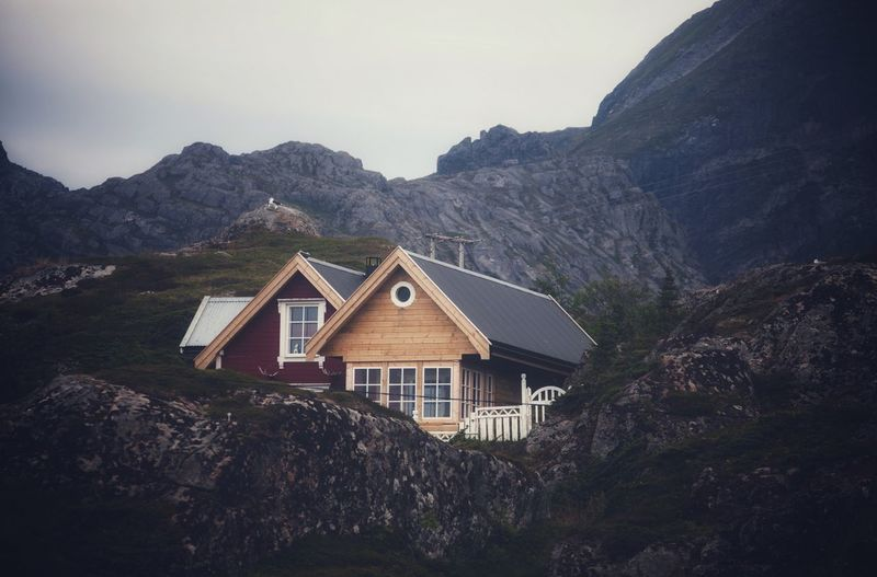 House Amidst Rocks And Mountains Against Sky