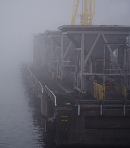 Machinery by the pier Railing Sea Pier Industry Building Exterior Reflection Water No People Built Structure Architecture Dirty Pollution Haze Hazy  Fog Foggy Port Harbour Heavy Duty Harbor Oily Machinery Waterfront Industrial Gh5