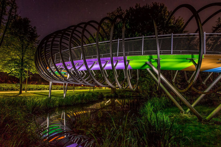 Illuminated park against sky at night