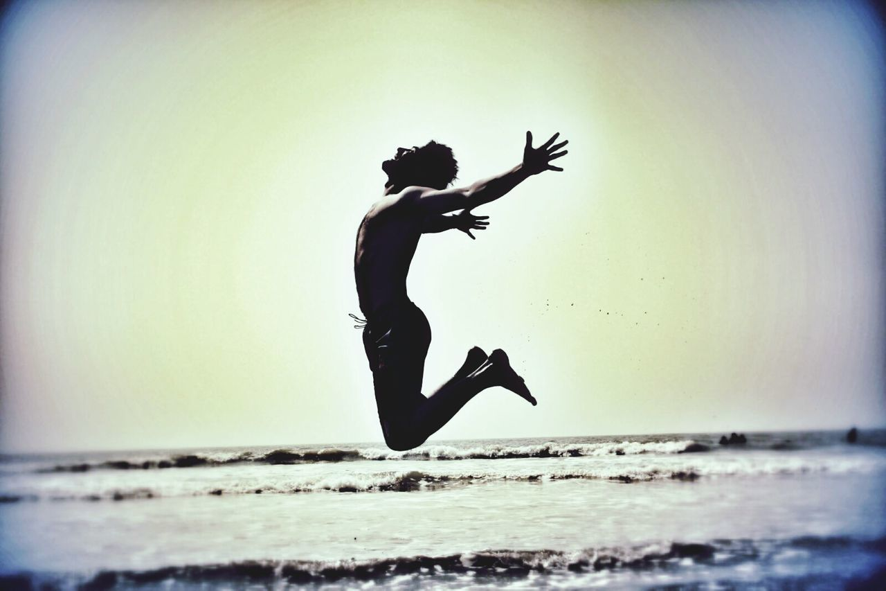 sea, jumping, mid-air, horizon over water, water, full length, silhouette, motion, real people, one person, beach, energetic, clear sky, lifestyles, outdoors, day, flying, wave, sky, nature, people