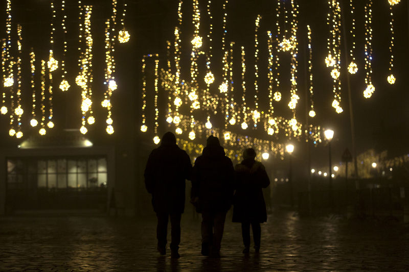 Rear view of people walking on illuminated lights at night