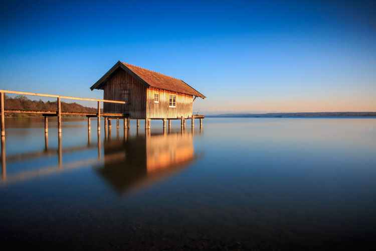 Stilt house in lake against clear sky during sunset
