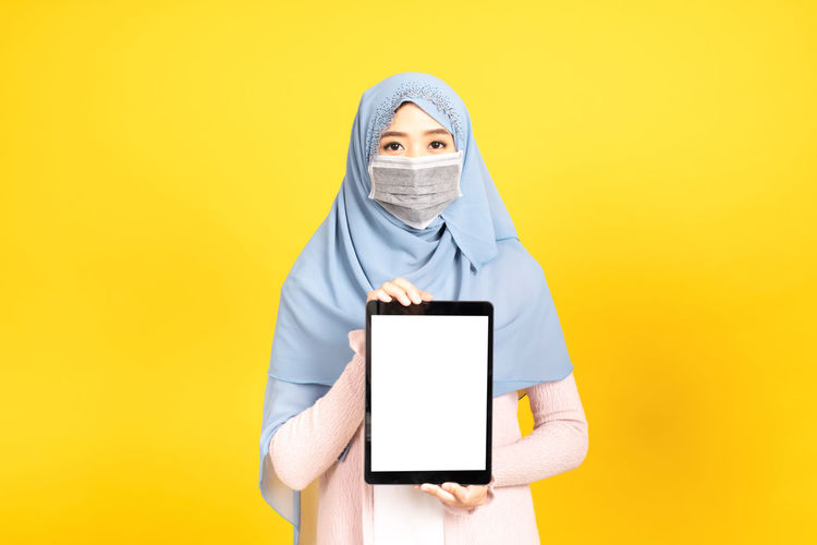 Portrait of person holding smart phone against yellow background