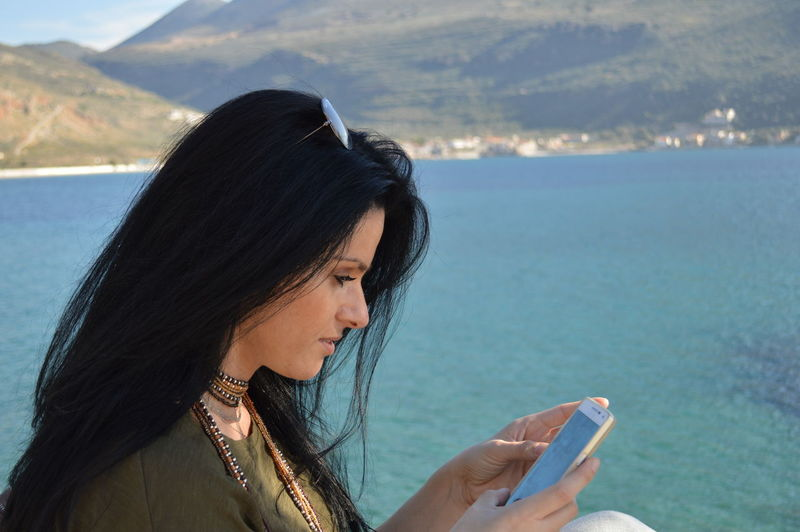 Side view of young woman using phone against sea