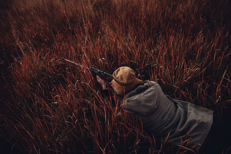 High angle view of man aiming rifle while lying on grassy field