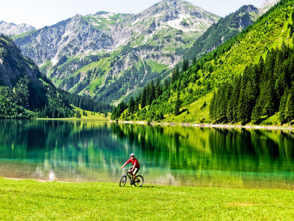 Adventure Beauty In Nature Bicycle Cycling Day Forest Full Length Grass Lake Leisure Activity Lifestyles Mountain Mountain Bike Mountain Range Nature Non-urban Scene One Person Outdoors Reflection Rocky Mountains Scenics Tranquil Scene Tranquility Tree Water