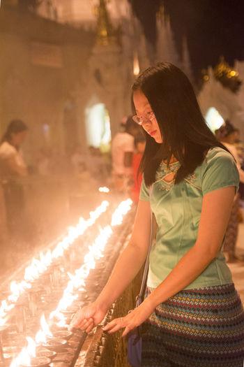 Woman Burning Diya At Temple