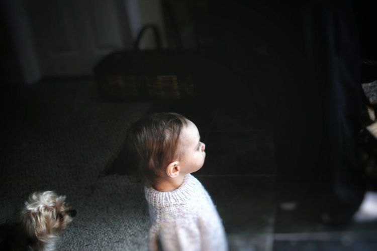 High angle view of cute baby girl looking away standing at home