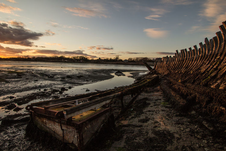 Old Ruins Of Boat At Beach During Sunset