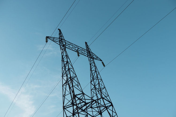 Low angle view of silhouette electricity pylon against blue sky