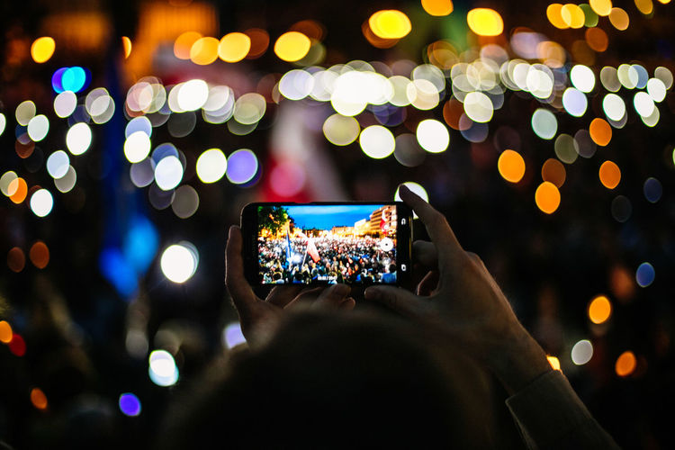 Cropped Hands Of Man Photographing Illuminated Protest At Night