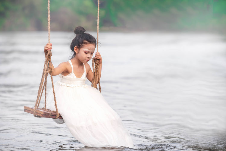 Girl sitting on swing over lake
