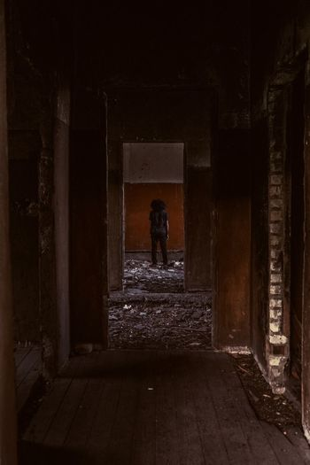 Rear view of man walking in abandoned building