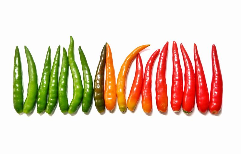 Close-up of chili peppers against white background