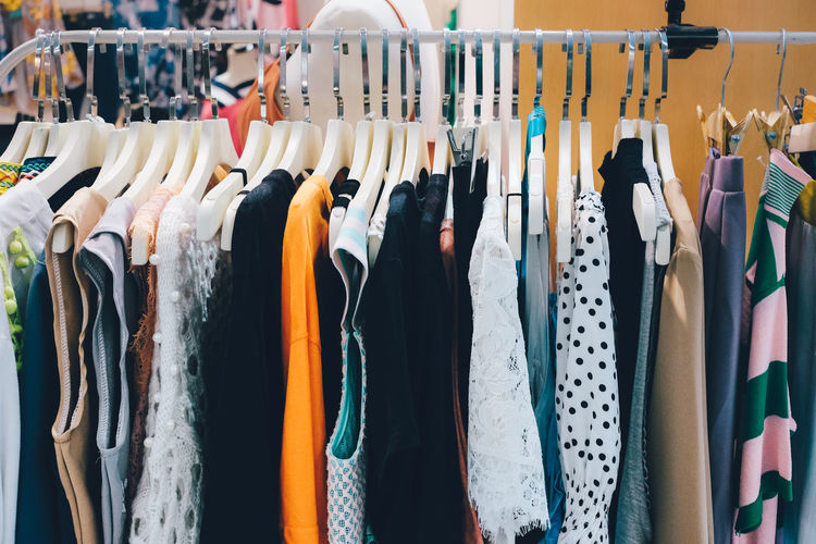 View of various clothes hanging for sale at market