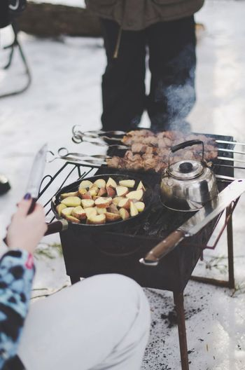 Cropped Image Of Woman Preparing Food On Barbeque Grill
