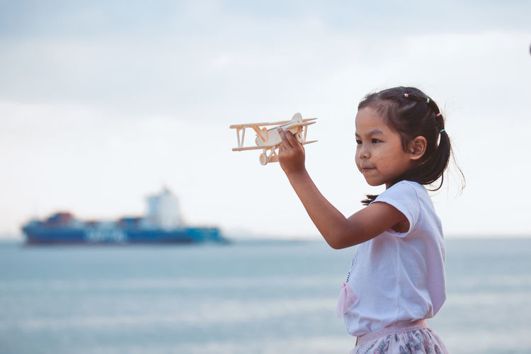Side view of girl holding toy airplane at beach against sky