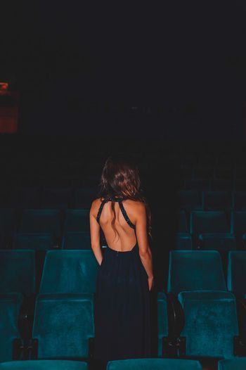 Rear view of woman wearing backless dress while standing by seats