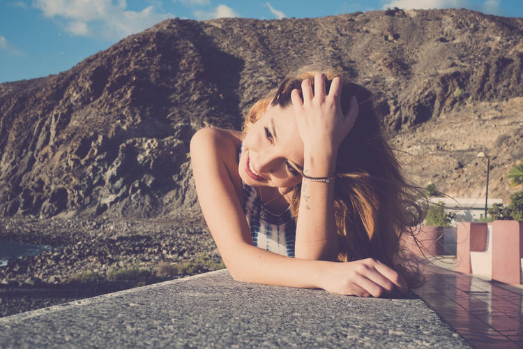 young woman smile and lay down on a wall near the beach in vacation Happiness Travel Vacations Wall Day Harmony Long Hair Lying Down Mountain One Person Outdoors People Real People Sea Sitting Sky Smiling Sun Tenerife Tensed Young Adult Young Women
