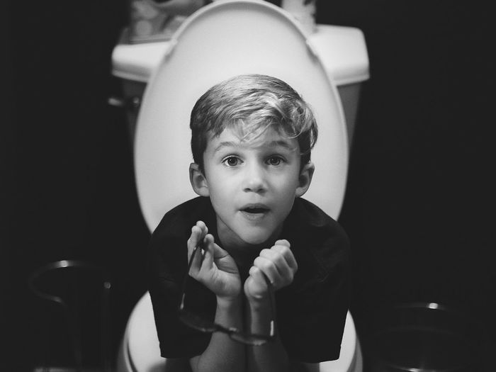Portrait of boy sitting on toilet bowl in bathroom