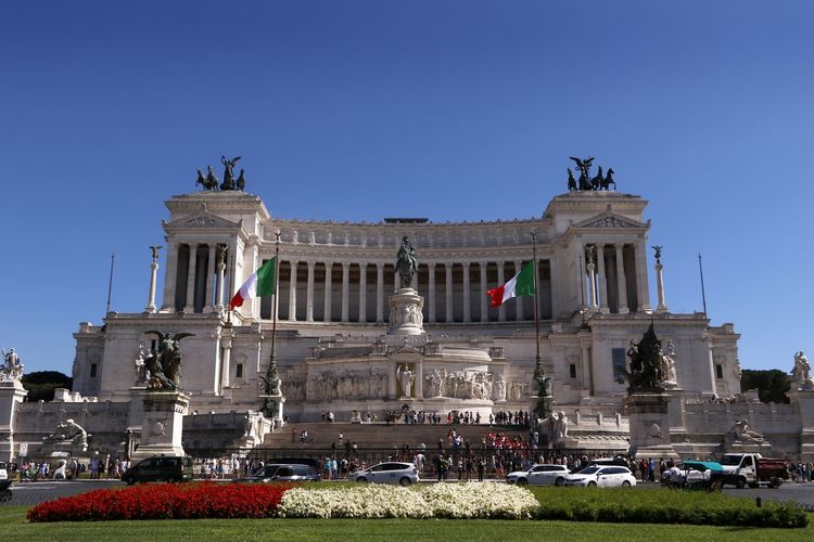 The National Monument to Victor Emmanuel II is a monument built in honor of Victor Emmanuel, the first king of a unified Italy, located in Rome, Italy and completed in 1925. Shrine Travel Photography Architectural Column Architecture Building Exterior Built Structure Car City Clear Sky Colonnade Grass History Human Representation Incidental People Mode Of Transportation Monument Nature Outdoors Sculpture Sky Statue Tourism Tourist Destination Travel Travel Destination