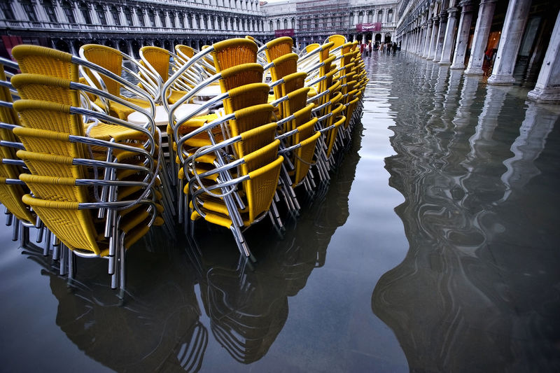 Yellow stacked chairs on water filled walkway during flood at piazza san marco