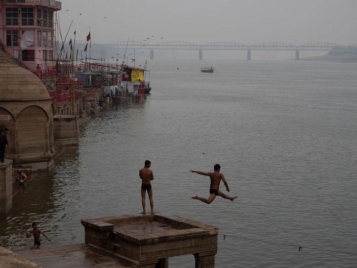 People on pier by sea against sky