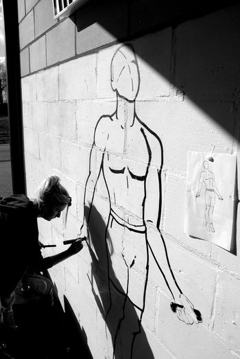 Shadow Real People One Person Sunlight Architecture Wall - Building Feature Built Structure Day Women Lifestyles Wall Creativity Adult Sitting Human Representation Casual Clothing Standing Outdoors Art And Craft Hairstyle