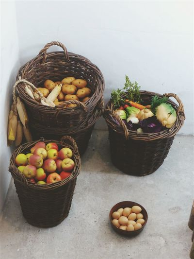 High angle view of fresh vegetables and fruits in baskets at home