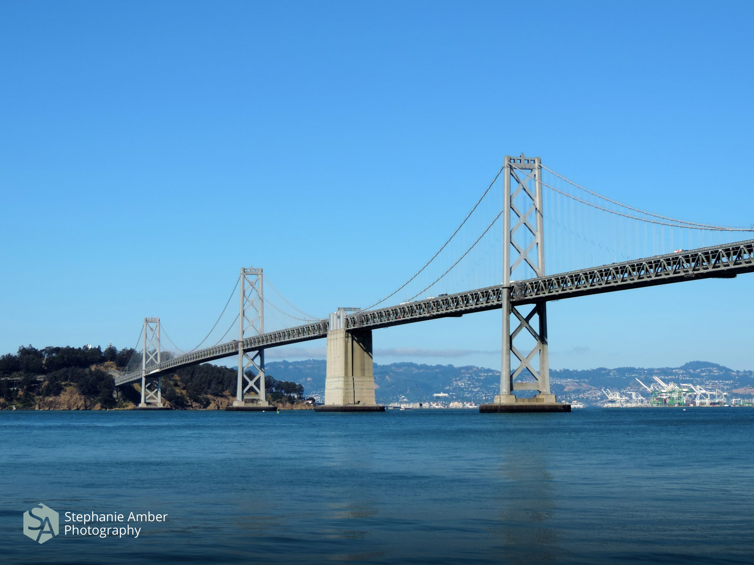 water, connection, built structure, architecture, transportation, bridge, sky, bridge - man made structure, engineering, blue, clear sky, suspension bridge, river, copy space, nature, day, travel destinations, waterfront, outdoors, bay, long
