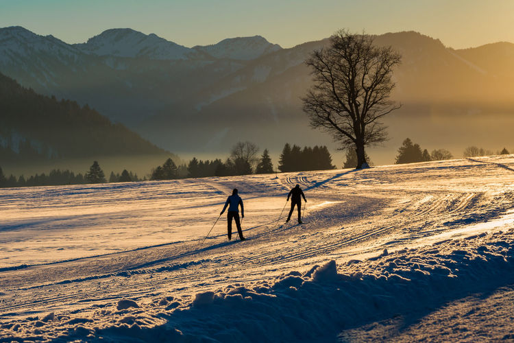 People walking on snowy field against mountains during winter
