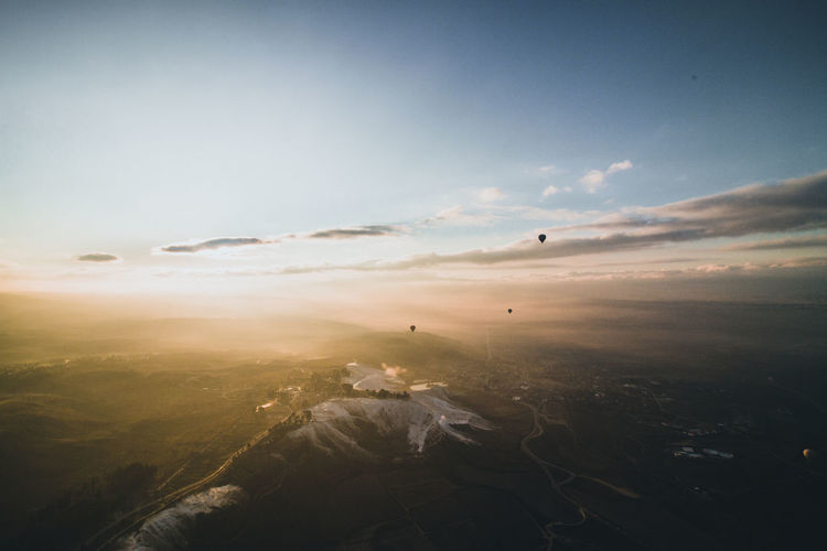 Hot air balloons flying over foggy landscape against sky during sunrise