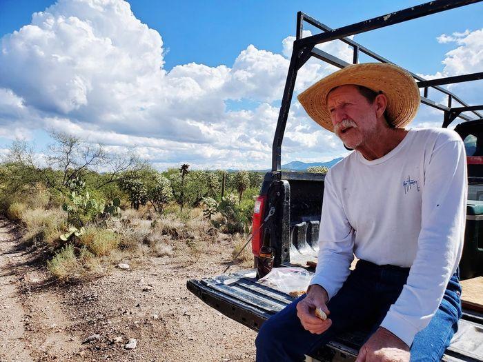 Full length of man sitting on landscape against sky