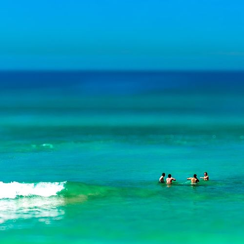 Friends swimming in sea against sky
