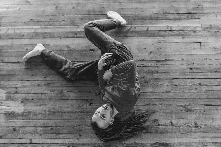 High angle portrait of man lying on hardwood floor