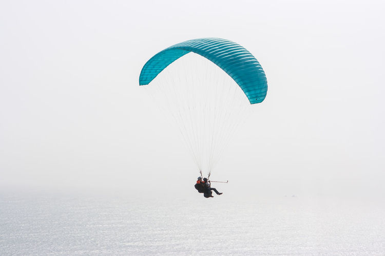High angle view of people paragliding over ocean against clear sky