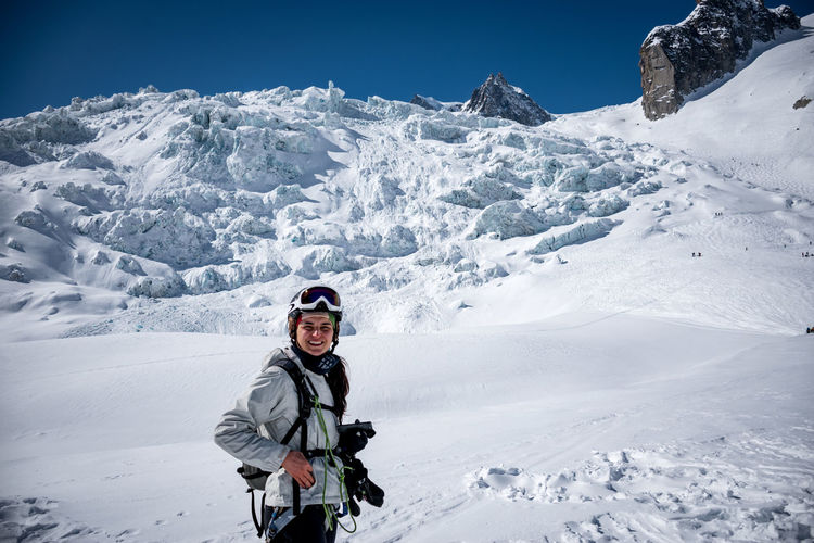Full length portrait of smiling man standing on snowcapped mountain