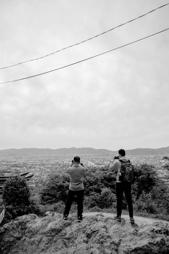 Rear view of men standing on land against sky