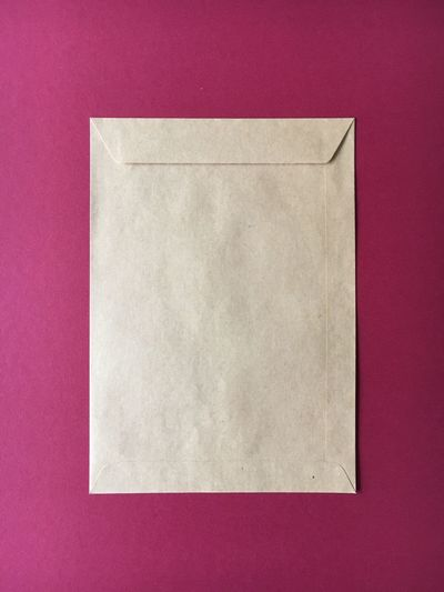High angle view of envelop on pink background