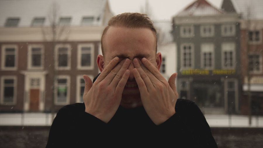 Portrait of person covering face with hand against built structure