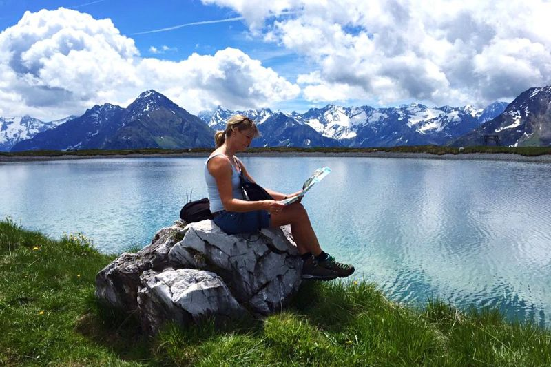 Side view of woman reading map while sitting on rock at riverbank against snowcapped mountain