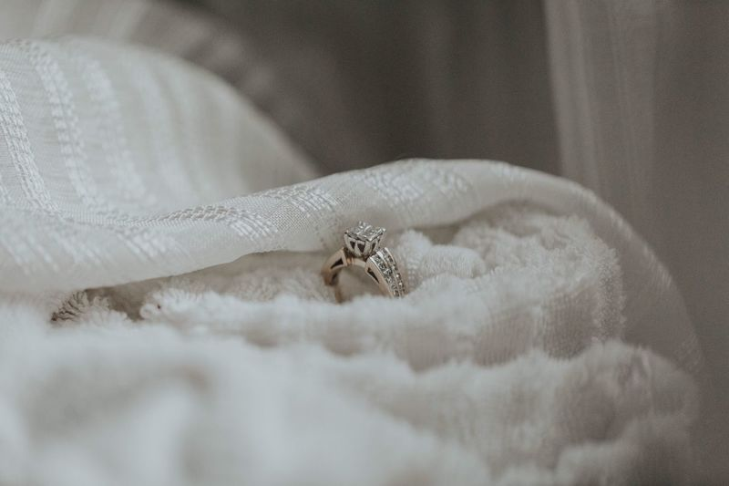 Close-Up Of Wedding Diamond Ring On White Fabric